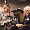 National Guard Capt. Wes Mathes presents WWII veteran John Denney, 90, with replacements of his service medals Friday morning at the Clarksville Library. Denney earned the Purple Heart, the Good Conduct Medal, the WWII Victory Medal and European-African-Middle Eastern Campaign medal. Denney lives in Charlestown. Staff photo by C.E. Branham