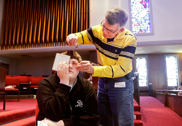 Optometrist Ron Nolan gives Thomas Dowdle, 16, an eye exam during the annual St. Mark's United Church of Christ Neighborhood Health Fair in New Albany on Saturday afternoon. Staff photo by Christopher Fryer