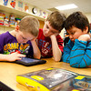Skylar Cunningham, Cade Beckingham and Jason Sanchez play a game on an iPad Mini that was donated to their class at Mount Tabor Elementary School on Friday. Dads Appreciating Down Syndrome of Kentuckiana donated four iPad Minis to the school with four OtterBox protective cases to the special needs classes at the school. Staff photo by Jerod Clapp