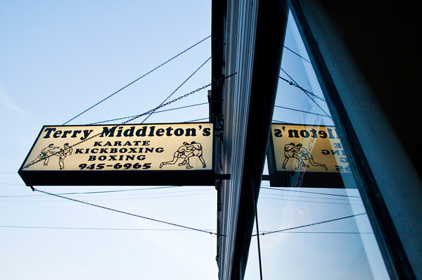 The sign for Terry Middleton's martial arts studio is reflected in the window of the business in downtown New Albany on Wednesday evening. Middleton offers training in boxing, kickboxing, mixed martial arts, and karate and has been in business for 40 years. Staff photo by Christopher Fryer