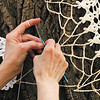 Pat DaRif, of Louisville, crochets vintage doilies together as part of a crochet bombing at the Carnegie Center for Art and History in New Albany on Wednesday afternoon. DaRif and five other fiber artists gathered at the Carnegie Center to cover trees, lampposts, urns, and other outdoor features in front of the building as an extension of Bette Levy's fine-art-embroidery show Tools of the Trade, which opened Friday and runs through April 28th. Staff photo by Christopher Fryer