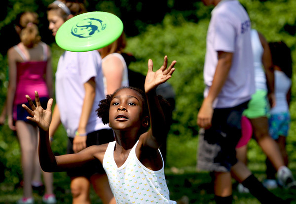 The Clarksville Parks Department Summer Playground Program celebrated the first day of summer with games and a picnic in Ashland Park. Nyla Cook, above, chased down a Frisbee at the event. Staff photo by C.E. Branham