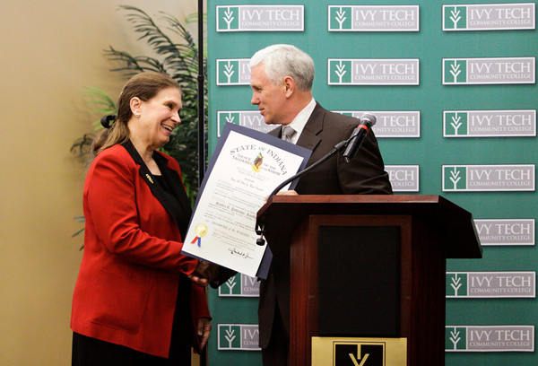 Indiana University Southeast Chancellor Sandra Patterson-Randles accepts the Sagamore of the Wabash award from Gov. Mike Pence following a ceremonial signing of two education bills at Ivy Tech Community College Southern Indiana on Wednesday afternoon. The award is the highest honor that Indiana governors can present, and Patterson-Randles received her's in honor of her retirement as chancellor from IU Southeast this year. Staff photo by Christopher Fryer