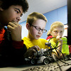 Steven Wimberly, 12, Chase Blalock, 10, and Cameron Mercer, 8, all of New Albany use a computer to program a Lego Mindstorms robot at the Ed Endres Boys & Girls Club in New Albany on Wednesday afternoon. The New Albany club is part of a 20 club pilot project created to promote basic programming and engineering skills through a partnership with Time Warner Cable, the Boys & Girls Club of America and FIRST Robotics. Staff photo by Christopher Fryer