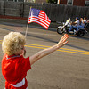 Joyce Riley, of Clarksville, waves an American flag while she greets motorcyclists escorting the American Veterans Traveling Tribute Vietnam Wall through Clarksville on a tour of the area on Wednesday evening. Staff photo by Christopher Fryer