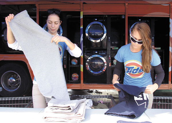 Olga Alkhutova, left, and Tiffany Tyree, both of Indianapolis, fold laundry as part of Tide's Loads of Hope program Wednesday afternoon in Henryville. Residents can drop off two loads of laundry per day and program staff will wash, dry and fold it. Staff photo by Christopher Fryer