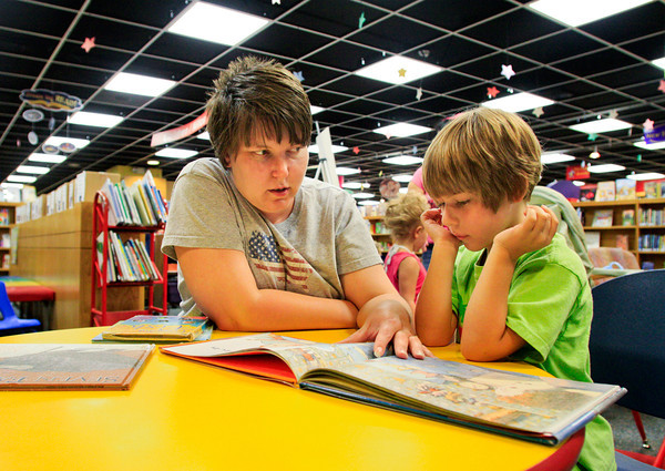 "Jill Cain, of New Albany, reads ""Oliver Who Would Not Sleep"" to her daughter Megan, 6, in the Childrens Department at the New Albany-Floyd County Public Library on Wednesday afternoon. Staff photo by Christopher Fryer"
