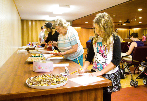Lily Brown, 9, Georgetown, marks down her vote for the people's choice award after sampling different dishes during the Bicentennial Bake-off in the Elsa Strassweg Auditorium at the New Albany-Floyd County Public Library in New Albany on Wednesday evening. Recipes for the dishes in the contest were from the New Albany Bicentennial Cook Book that was released late last year. Three judges were on hand to award the first, second and third place prizes, and participants and audience members were given the opportunity to vote for the people's choice award. Staff photo by Christopher Fryer