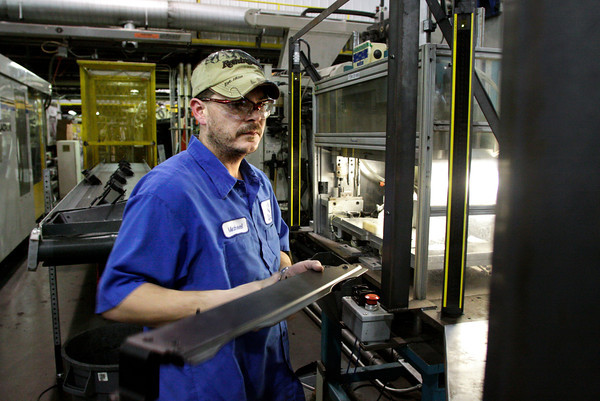 Mold shop operator Michael Goodman, of Jeffersonville, works on radiator brackets in the manufacturing facility at the New Albany location of Beach Mold & Tool on Wednesday afternoon. Staff photo by Christopher Fryer