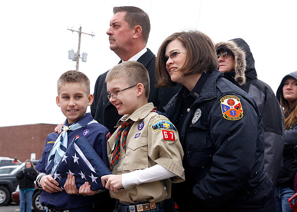 Christian and Caleb Daily hold a United States flag with Major Chuck Adams of the Clark County Sheriff's Department and Rachel Bussey with the New Washington Volunteer Fire Department during a commemorative ceremony for Henryville on Saturday. The town celebrated the recovery efforts a year after an EF-4 tornado destroyed homes and the community's schools. Staff photo by Jerod Clapp