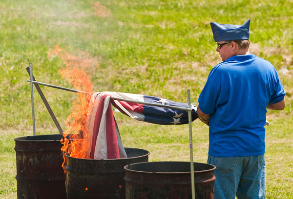 Jim Hobbs, of New Albany, retires an American Flag while working on the flag detail during the 40 & 8 Voiture 1250 Society's annual flag retirement ceremony in New Albany on Saturday afternoon. Staff photo by Christopher Fryer