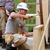 AmeriCorps worker Brandon Gutteridge nails wall frame segments together for a Habitat for Humanity storage facility in Henryville. Staff photo by C.E. Branham