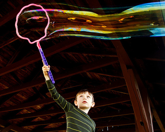 Joel Allgeier Jr., 6, of Sellersburg, plays with his little sisters giant bubble wand under a shelter at Sam Peden Community Park in New Albany on Monday afternoon. Staff photo by Christopher Fryer