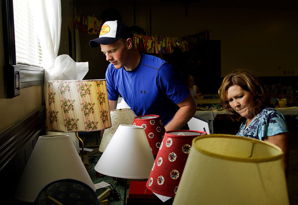 Junior leader Justin Miller, 17, of Corydon, assists judge Sallie Plass, right, as she looks over lamps made with used books for a recycling project during preliminary judging of the Floyd County 4-H Fair in Newlin Hall at the fair grounds in New Albany on Thursday afternoon. Staff photo by Christopher Fryer