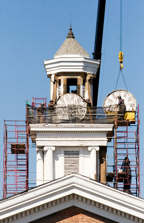 A crew with D & M Masonry load clock faces onto a crane to be lowered  from the tower on top of the Second Baptist Church along Main Street in downtown New Albany on Friday afternoon. The company removed the clock faces and other decorative elements from the tower to be restored in a shop off site. Staff photo by Christopher Fryer