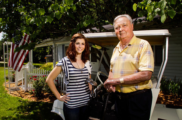 David Keller stands with his granddaughter Ashley Keller in front of his home in Floyds Knobs on Tuesday afternoon. Keller was the recipient of a double lung transplant in 2007 and this month marks the anniversary of his surgery. Staff photo by Christopher Fryer