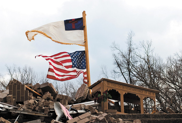 Flags fly above what is left of the Mt. Moriah Church in Henryville Sunday afternoon. Staff photo by Christopher Fryer