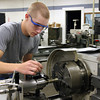 Ryan Stonecipher, a junior from Corydon Central High School, makes a jack screw on a metal lathe at the Prosser Career Education Center. The school has changed its name from the Prosser School of Technology to better reflect its mission. Staff photo by Jerod Clapp