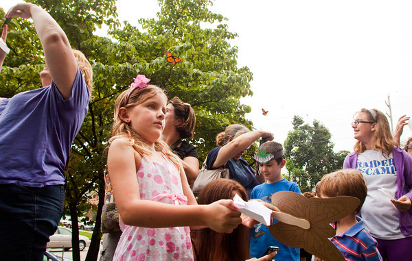 Haley Gilbert, 7, New Albany, participates in the release of 250 Monarch butterflies during the annual Monarch Celebration at the Arts Council of Southern Indiana in New Albany on Saturday afternoon. Staff photo by Christopher Fryer