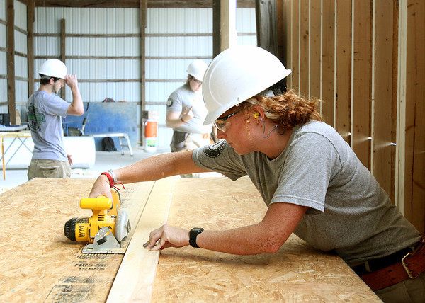 AmeriCorps worker Sara Butler cuts a shelf at the former Tallent Lumber site in Henryville Thursday afternoon. AmeriCorps workers are building a secure storage area to house supplies for Habitat for Humanity homes that will be built in October. Staff photo by C.E. Branham