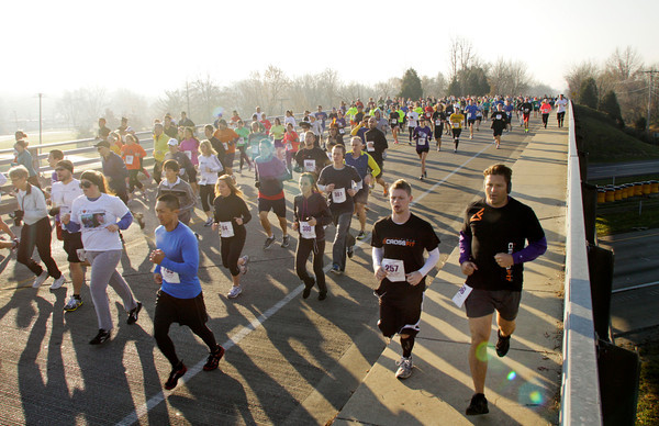 Runners make their way across the Interstate 265 bridge on Green Valley Road at the start of the 24th annual Fast Freddie's Festive Five-Mile Foot Feast in New Albany on Thursday morning. More than 1,100 participants registered for the event, which surpassed the 2009 record of 1,041. Staff photo by Christopher Fryer
