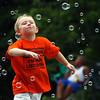 Payton Carrol runs through bubbles at the Cross Creek Apartments youth fun day Saturday afternoon. Staff photo by C.E. Branham