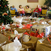 Gift bags sit beside a Christmas tree in the lobby of Yellowwood Terrace while staff members and volunteers prepare to hand them out to residents on Wednesday afternoon in Clarksville. About 120 gift bags were given out at the event through Home Instead Senior Care's Be A Santa To A Senior program. Staff photo by Christopher Fryer