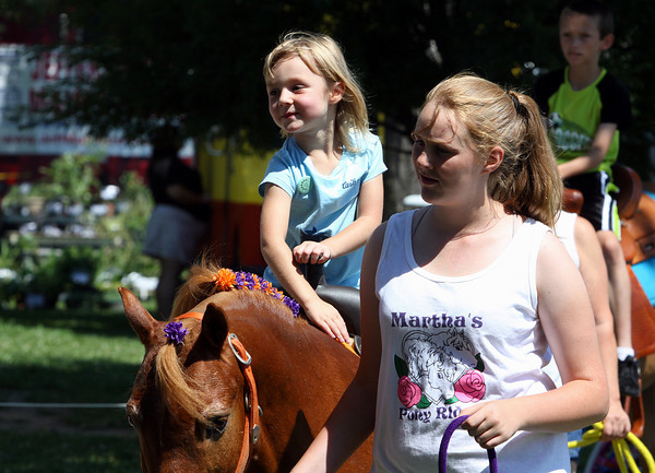 Mylie Swinney pets the pony she was riding at JEFF Fest on Saturday in Jeffersonville's Preservation Park. Staff photo by C.E. Branham