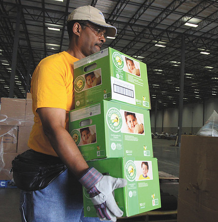 Adventist Community Services volunteer Henry Martin carries diapers from a shipment received Monday at the warehouse. Staff photo by C.E.. Branham