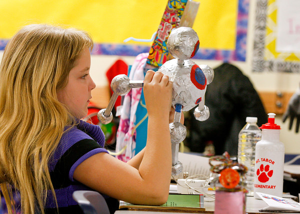 Sarah Starkey, a third-grader at Mount Tabor Elementary School, makes some final adjustments to her robot, Growl. Students at the school built robots that would solve problems in their own lives out of household items  and spoke to other students about what they did. Staff photo by Jerod Clapp
