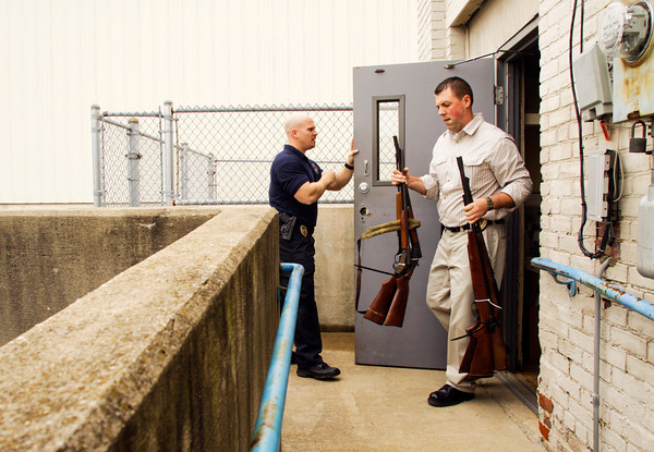 Officer Kris Ferrell holds the door for officer Cody Wooten as he carries firearms to a truck after they were purchased during a buyback program at the Ekin Avenue Recreation Center in New Albany on Friday afternoon. The buyback lasted less than two hours and 249 firearms were purchased before the $50,000 ceiling for the program was reached. Staff photo by Christopher Fryer