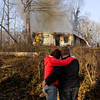Amanda Myers, of Jeffersonville, consoles her boyfriend Billy Fulkerson as they watch New Chapel firefighters battle a fire that engulfed his home located at 2058 Two Mile Lane on Wednesday afternoon in Floyd County. No injuries occurred during the fire. Staff photo by Christopher Fryer