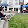 Erin Fletcher a volunteer with the New Albany Public Art Walk, watches a musician perform while it rains. The wet weather stopped, which helped generate more foot traffic for the event. Staff photo by Jerod Clapp