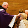 Father Joseph West marks the forehead of Polly Senzig, of Clarksville, during Ash Wednesday mass at St. Anthony Padua Catholic Church in Clarksville. Ash Wednesday marks the beginning of Lent, a period of penitence and fasting that lasts for 40 weekdays until Easter. Staff photo by Christopher Fryer