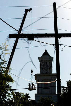 Contractors Dave, left, and Frank Delbridge look over the clock tower and front facade of the Second Baptist Church during a structural analysis of the historic building in downtown New Albany on Wednesday morning. Staff photo by Christopher Fryer