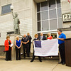 R.T. Jefferson, far right, the Kentucky and Indiana state manager for the non-profit fraternal benefit society Woodmen of the World, presents New Albany Chief of Police Sherri Knight with a 9/11 Flag of Honor during a ceremony in front of the New Albany Police Department on Wednesday morning. The red and white stripes of the American flag consist of the names of the victims of the Sept. 11 terrorist attacks. Staff photo by Christopher Fryer
