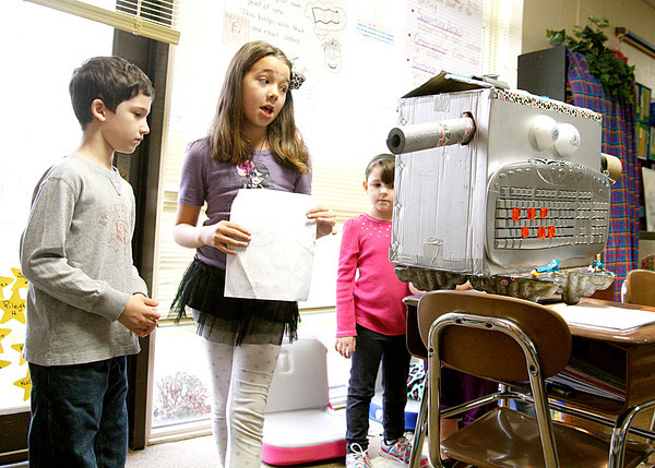 Isabelle Vittitow, third-grader at Mount Tabor Elementary School, demonstrates her homework completing and grading robot, Larry, to Braedan Quinn a first-grader. Third-graders built their own robots to solve various problems in the school's annual Robot Museum, then presented them to others in the school. Staff photo by Jerod Clapp