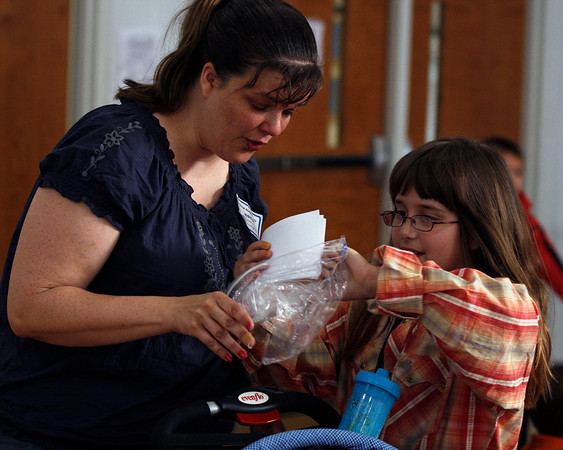 Kimberly Baumgarten gives her daughter, Katie, a plastic bag to hold the note cards for her speech at Utica Elementary School's school-wide oratorical. Katie, a third-grader at the school, has autism, but doesn't let it slow her down. Staff photo by Jerod Clapp