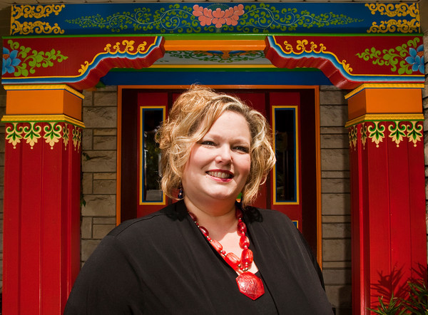 Lisa Morrison, the director of marketing and media at the Tibetan Mongolian Buddhist Cultural Center in Bloomington, stands in front of the Drepung Gomang Institute in Louisville last week. Staff photo by Christopher Fryer