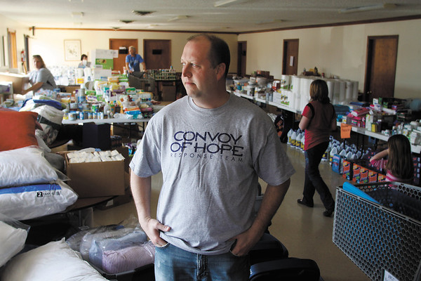 Pastor Rich Cheek stands in the basement of the Henryville Community Church Wednesday afternoon where many groceries and toiletries are available for tornado victims in the area. The church is also distributing and supplying building materials and providing 1500 meals a day. Staff photo by Christopher Fryer
