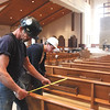 Tom Basler, foreground, and Corey Miller set pews in the new St. Mary of The Knobs Catholic Church.  Staff photo by C.E. Branham