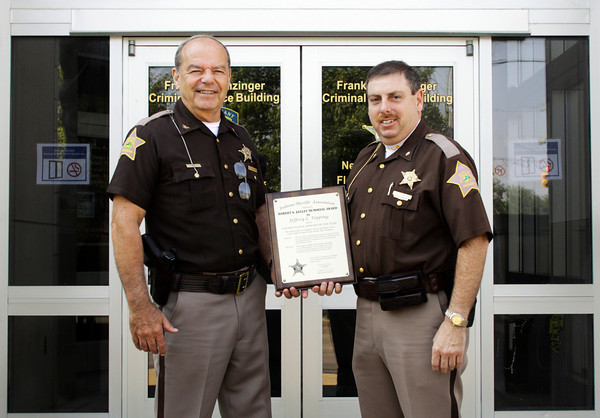 Floyd County Police Chief Ted Heavrin, left, stands with Indiana Sheriffs' Association County Police Officer of the Year award recipient, Detective Major Jeffrey Topping, in front of the Frank C. Denzinger Criminal Justice Center in New Albany on Tuesday morning. Staff photo by Christopher Fryer