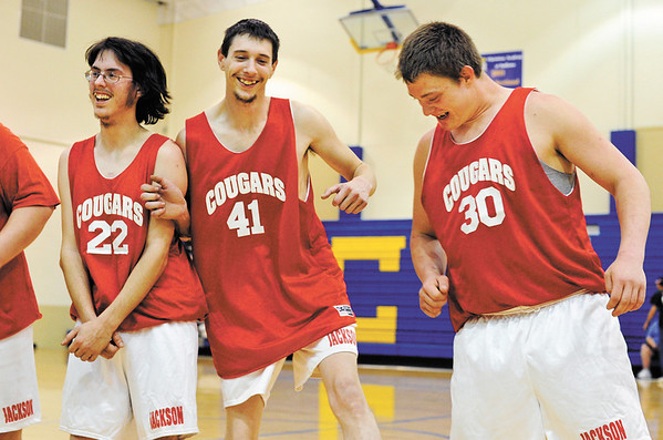 Jackson County players Matt Kedrowitz, Charlie Girts and Dwight Phillips horse around on the court after winning their game against the Harrison County Showstoppers during the Special Olympics Area 2 Sectional basketball tournament at Christian Academy on Saturday afternoon. Their win advanced the Cougars to the state tournament at Indiana State University in Terre Haute on March 24th and 25th. Staff photo by Christopher Fryer