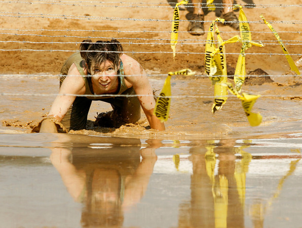 Megan Breier, of Louisville, keeps her eyes on the barbed wire as she makes her way through the final obstacle of the Muddy Fanatic 5K Adventure Race at the former Glenwood Training Center in Sellersburg on Saturday morning. Over 2000 participants negotiated over 30 obstacles on a 3.1 mile course either as individual racers or as part of a team. Staff photo by Christopher Fryer