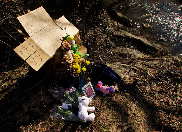 A memorial to Jaime Clutter and her two children, Brandon, 10, and Katelyn, 6 months, sits next to Falling Run Creek in Binford Park on Thursday afternoon in New Albany. The three were found dead in the creek on March 13. A visitation and funeral service were held at Greater Faith Church in New Albany on Saturday. News and Tribune photo by Christopher Fryer