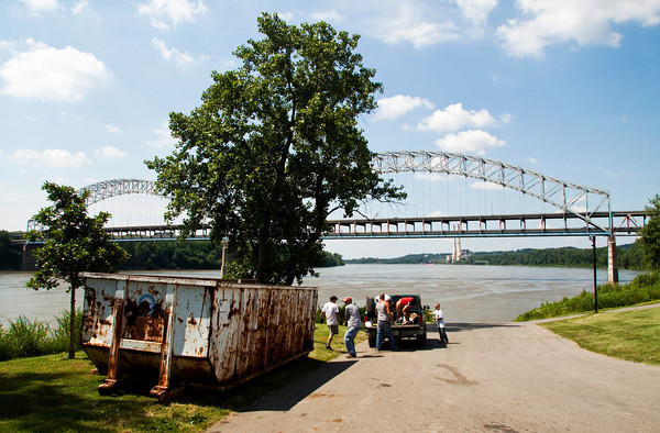 Volunteers move junk and debris to a dumpster on the New Albany riverfront during the 2013 Ohio River Sweep in New Albany on Saturday morning. Staff photo by Christopher Fryer