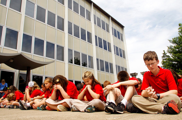 Members of the Christian Academy fifth grade choir pray during a service in observance of the annual National Day of Prayer on the lawn of the City-County Building in New Albany on Thursday afternoon. Staff photo by Christopher Fryer