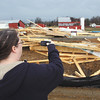 Teresa Dorman photographs a partially built home in Jeffersonville at the Village at Armstrong Farm that was flattened by a storm Tuesday morning.  Staff photo by C.E. Branham