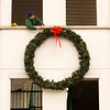 Bill Dickens, New Pekin, with the New Albany Street Department, hangs a wreath from the parking garage at the corner of State and Market streets in downtown New Albany on Tuesday morning. Staff photo by Christopher Fryer