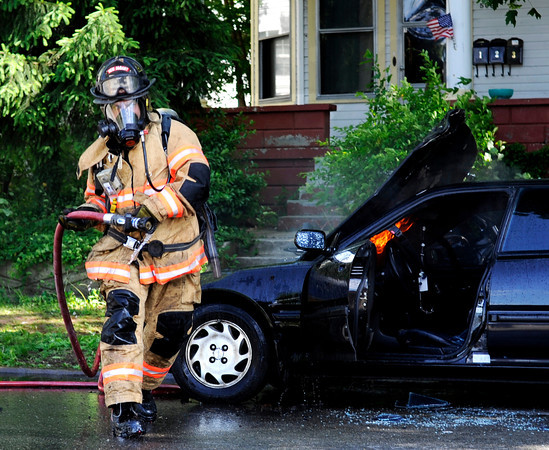 A New Albany firefighter pulls a water hose around to extinguish flames coming from the engine of an Acura sedan parked in front of the residence at 506 E. Main St. on Monday afternoon. Staff photo by Christopher Fryer